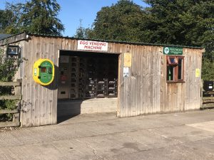 Photo of the outside of Anslow Egg Vending Machine with the Defibrillator unit installed on the outside wall.